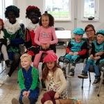 Kinderen op de foto met twee zwarte pieten