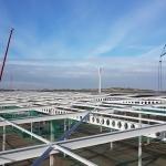 Staalconstructie van bovenaf met bouwkranen op achtergrond