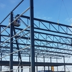 Monteurs van Holland Staal in hoogwerkers die staalconstructie bouwen