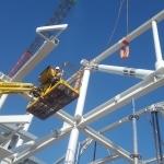 Monteur in hoogwerker bouwt aan staalconstructie
