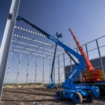 Bouw van staalconstructie met kraan en twee hoogwerkers