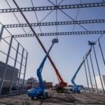 Bouw staalconstructie met hoogwerkers en kraan
