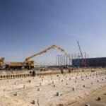 Bouwplaats met betonstortwagen en stalen constructie met kraan